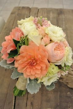 Bridal bouquet with peach dahlias, garden roses, lisianthus,stocks, skimmias and dusty millers. Designed by Forget-Me- Not Flowers in Banff