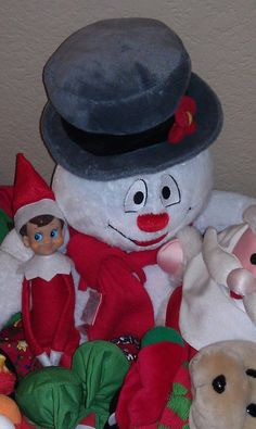 Elf on the Shelf hanging out with some of his stuffed animals friends..