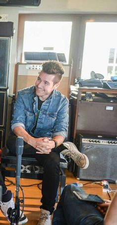 Dan Smith of Bastille, smiling, with his legs crossed, in his jean jacket