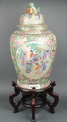 """Lot 127, A 20th Century famille rose baluster vase and cover decorated with figures in pavilions on a ground of insects and flowers with lion finial 24"""" on a hardwood stand Est £200-300"""