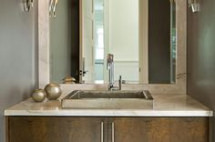 Elegant powder room design with unique, textured sink basin. 1 of 4 projects by Susan Marinello Interiors.