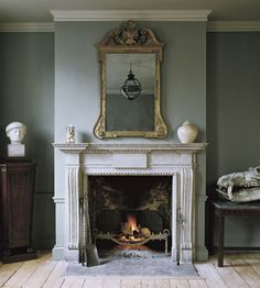 ~Jamb - The Chesham chimneypiece in distressed Portland stone with the Arts and Crafts fire basket and Stockton fire irons. A small Original Globe is reflected in the mirror. Vintage Fireplace, Victorian Fireplace, Home Fireplace, Living Room With Fireplace, Fireplace Surrounds, Fireplace Design, Fireplace Ideas, Antique Fireplace Mantels, Antique Mantel