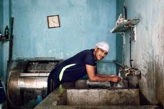 He seems to be an operator of the handmade washing machines (in the back) in Indian laundry. Some heavy look there.