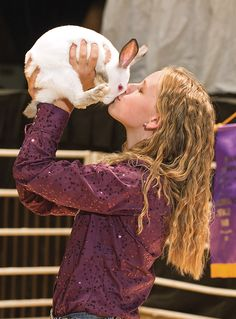 Sydney Baty, of Loveland, gives one of her grand champion rabbit a kiss during the 2012 Junior Livestock Sale at the Colorado State Fair. Chieftain photo John Jaques 8.28.12