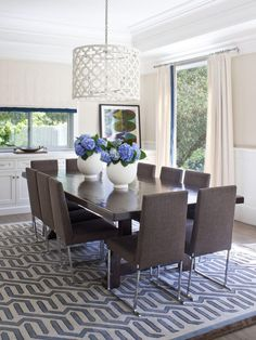 Ten brown upholstered chairs add a lively, fun note to this contemporary family dining room, which was built with durability and easy cleaning in mind. The blue-and-white graphic area rug is mimicked in the centerpiece of blue hydrangeas in white vases. Ledge for artwork