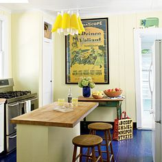 Detailed Cottage Kitchen: The charm of this lakeside cottage kitchen lies in its attention to detail. The previously linoleum-covered floors were ripped up in favor of this rich blue color, echoed again in a vase of hydrangeas. An ultramodern light fixture paired with the old-school movie poster is a refreshing mix of old and new