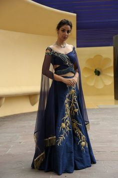 Midnight blue raw silk lehenga with angel cape sleeves with the details of fringes on the waist and tassels on the cape. Material: Georgette, Lycra Net Dry Clean Only Lehenga Choli Designs, Lengha Choli, Lehenga Blouse, Sarees, Indian Wedding Outfits, Bridal Outfits, Indian Outfits, Off Shoulder Lehenga, Raw Silk Lehenga