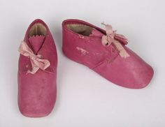 A pair of bright pink leather baby shoes with pale pink ribbons, made in 1851.