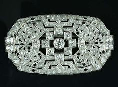 An art deco diamond plaque brooch, circa 1930,  set to the centre with an old brilliant-cut diamond within a rubover collet, to a pierced surround of geometric and stylised foliate motifs millegrain-set with single and old brilliant-cut diamonds, four diamonds deficient, diamonds approximately 7.40 carats total, length 7.0cm.