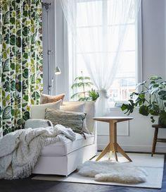 화이트 긴의자와 보조테이블이 놓여있는 화이트색 공간. 커다란 창문은 식물과 화이트/그린 텍스타일로 꾸몄어요.