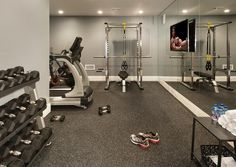 Basement gym features a mirrored accent wall lined with a flat panel tv facing workout equipment.