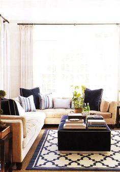 (sigh- this looks like the couch i didn't buy... Why?!) sand beige & navy blue comfy living room design with white paint wall color. White cotton drapes, sand beige modern velvet sectional sofa, blue throw pillows, stripe blue throw pillows, square velvet blue ottomans with nailhead trim nailhead trim, blue & white Moroccan rug, jute rug and wood end tables coffee tables.