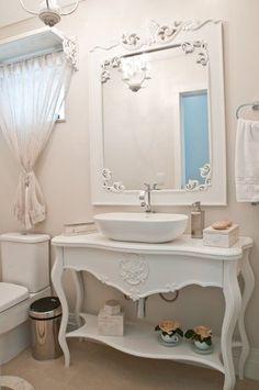 Já o lavabo exibe estilo provençal, com mobiliário na cor branca. A bancada da pia foi formada por um aparador e cuba oval. Sobre a janela, uma prateleira garante um delicado acabamento com a cortina.: