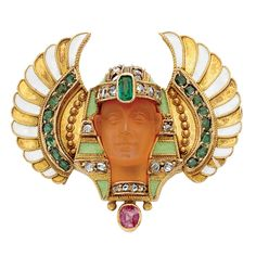 Egyptian Revival Gold, Carved Carnelian, Diamond and Enamel Pin - The stylized pharaoh's head of carved carnelian, with a rose-cut diamond-set headdress, accented by an emerald and a ruby and bands of green enamel, flanked by matte gold panels with a line of small gold balls and curved bands of emeralds, further edged by tapered flared curved panels of alternating gold and white enamel, circa 1865, with maker's marks.