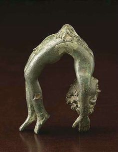 A FINE ROMAN BRONZE FIGURE OF AN ACROBAT, after an Etruscan example.