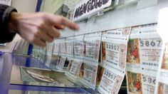 Una compradora elige un número para el Sorteo de la Lotería de Navidad en una administración