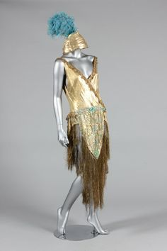 1920s dance/cabaret outfit of gold beaded cloth; the matching turban labeled 'A Fonnesbech, Copenhagen', the dress trimmed with gold bobbin-lace, the skirt with ornate rhinestone studded and beaded center-panel, the matching turban with feather and tulle cockade. Via Henning Thorsen collection.