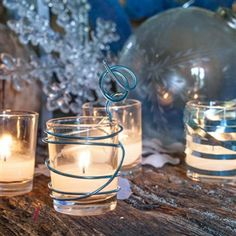 DIY simple Votive Candle Holders!  Grab some Decorative Wire, scissors, and some clear glass votive holders and get to wrapping.  Create fun, festive looks around your votive holders.  Pick a color that works with your theme.  The look created once the candle is lit is so festive as the light dances out the sides of the shapes created!  Now that's an easy DIY!