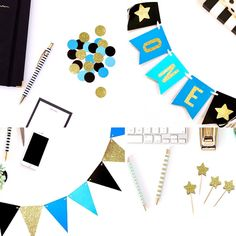 New first birthday party in a Box! Matching blue, black, and gold glitter banners, confetti, and cupcake toppers make your little one's big day extra special!