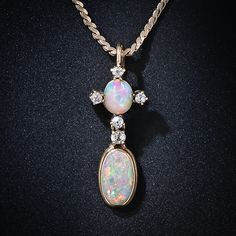 A relatively small, but exceedingly multi-chromatic, pair of fiery opals scintillate with electric confetti colors and are aided and abetted by six tiny European-cut diamonds in this truly lovely, Arts & Crafts influenced drop necklace dating back to the turn-of-the-twentieth century. 18 karat yellow gold; 7/8 inch long; the 14K chain measures 17 inch