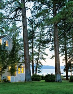 Jenni Kayne's Lake tahoe House | gray house in the woods on a lake at sunset