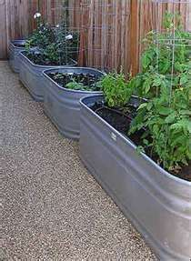 Idea for a raised bed along the breezeway walls. How cute would this be with flowers and herbs and antique furniture!