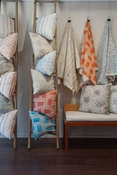 Very interesting use for ladders! Display pillows or scarves in your retail location with vintage ladders.