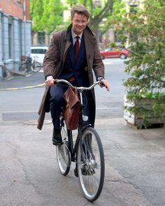 brown coat, blue cardigan and burgundy tie. and bike.