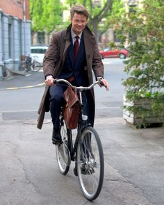 brown coat, blue cardigan and burgundy tie. and bike.