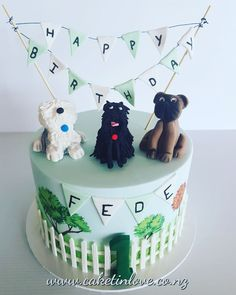 "A 8"" vanilla cake filled with chocolate ganache and decorated with pettinice fondant dogs, bunting and fence with handpainted details"