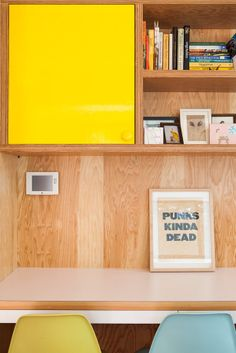A yellow cabinet stands out against a plywood backdrop in this Eagle Rock home.
