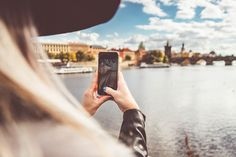Young Woman Taking a Photo with Her iPhone Free Stock Photo