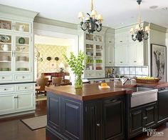 This traditional-with-a-twist kitchen was inspired by classic Hamptons architecture. A glaze on the custom flat-panel cabinetry and crown molding heighten intricate detailing. Chicken wire adds interest to the hutchlike built-in cabinets that flank the entry to the dining room. White bronze hardware provides a honed finish.