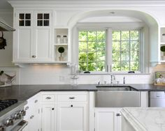 Kitchen: white kitchen, black counter top, glass cab fronts, cab style