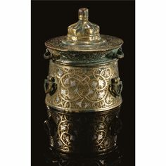 90 A SMALL KHURASAN SILVER-INLAID BRONZE INKWELL, EASTERN PERSIA, CIRCA 1200 Estimate: 5,000 - 7,000 GBP the cylindrical body applied with three loops handles, the cover with a central domed section surmounted by a bud finial, three loops applied around the edge, inlaid and incised decoration with a central band of sinuous foliate stems around the body, minor scrolling bands around the cover, the base with a central knot motif enclosed by scroll-filled cartouches Quantity: 2. 8.9cm.