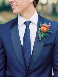 Chic Groom Attire  Not only are we obsessed with this groom's mum and fern boutonniere, but we also love his navy blue suit and paisley patterned necktie.
