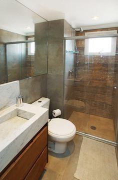 O banheiro social também ganhou tampo em pedra construída. Um porcelanato que imita madeira reveste uma das paredes internas do box.