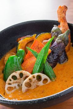 Flavorful soup curry with curry salt dusted vegetables and chicken, a specialty of Sapporo, Japan.