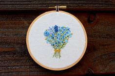 Something old, something new, something borrowed, something blue.  A variety of 5 or 6 delicate blooms are lovingly embroidered on natural cotton canvas in this 4 vintage metal spring hoop. Each flower is meticulously stitched in shades of blue, turquoise and green, with touches of mustard yellow.  This hoop comes ready to hang or is perfectly sweet perched on a shelf. Your bouquet hoop is backed in light blue kona cotton.  This hoop is ready to ship and will come carefully and beautifully…