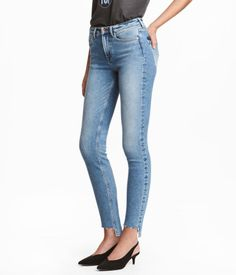 Denim blue. Slim-fit, ankle-length jeans in washed stretch denim with distressed details, regular waist, and zip fly with button. Front pockets, back