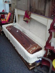 So many questions unanswered, such as …    1. Where the hell does someone find a vintage casket?  2. Why would someone want a vintage casket?  3. Yes, there's a musical instrument inside that is suspiciously similar in size, but this is clearly a casket.  4. Why are there stains on the inside?  5. What the hell?   6. Why is this even for sale in an antique shop, of all places?