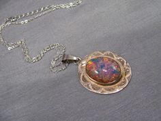 This Colorful Vintage Mexican Sterling Silver pendant is wonderfully iridescent. This pendant is adorned with a large glass opal stone. This