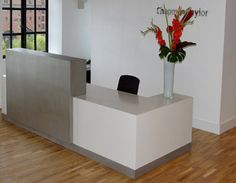 Bespoke Corian and bead blasted stainless steel reception desk.