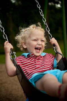 Laughing child swinging on a swing, in the park.