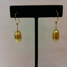 A pair of light golden south sea pearl drops earrings in 14k yellow gold.  Good luster