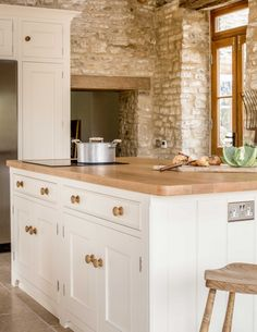 Sustainable Kitchens - A Traditional Country Kitchen. 17th Century Grade II listed barn conversion with oak worktops and cabinets painted in Farrow & Ball Tallow. The cabinets have traditional beading and mouldings and varnished oak knobs. The 300 year old exposed bricks help maintain the traditional style. The island has a tongue and groove end panel.