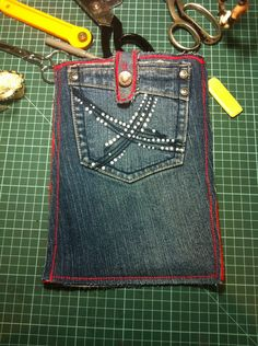 Upcycled denim and red felt tablet pocket, with cross stitch detail around the edges.