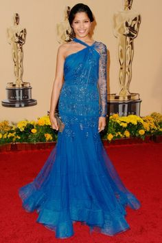 FREIDA PINTO  Freida Pinto brought a touch of Bollywood to the Oscars 2009 red carpet in a blue beaded John Galliano gown. The actress topped off the exquisite one-armed dress with a metallic Judith Leiber clutch. (2009)