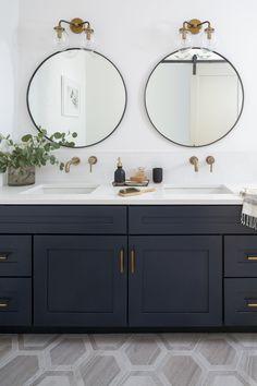 Navy double vanity bathroom with brass fixtures and round mirrors. Hexagon tile floor.
