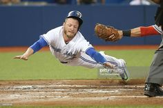 Josh Donaldson #20 of the Toronto Blue Jays slides safely across home plate to score on a sacrifice fly in the second inning during MLB game action as Yan Gomes #10 of the Cleveland Indians reaches with an attempted tag on September 2, 2015 at Rogers Centre in Toronto, Ontario, Canada.